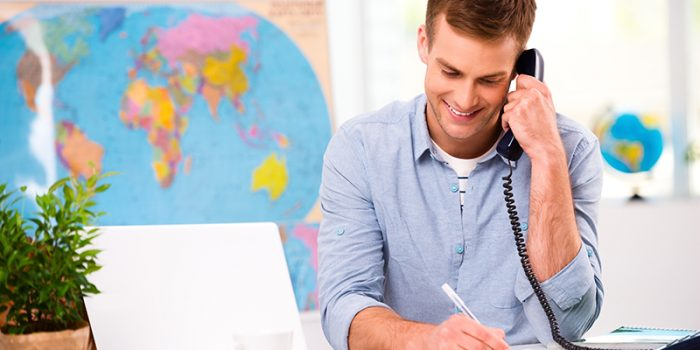 Photo of male travel agent. Young male operator smiling, talking on phone and offering vacation options for client. Travel agency office interior with big world map